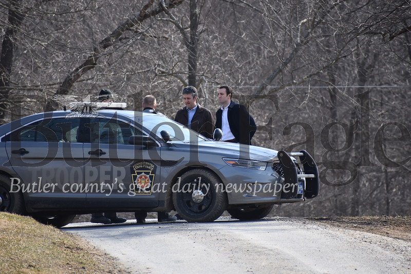 Assistant District Attorneys Benjamin Simone and Robert Zanella meet with state troopers on Davis Road where a a 23-year-old man was killed in what police say was a homicide. photos by Eric Jankiewicz