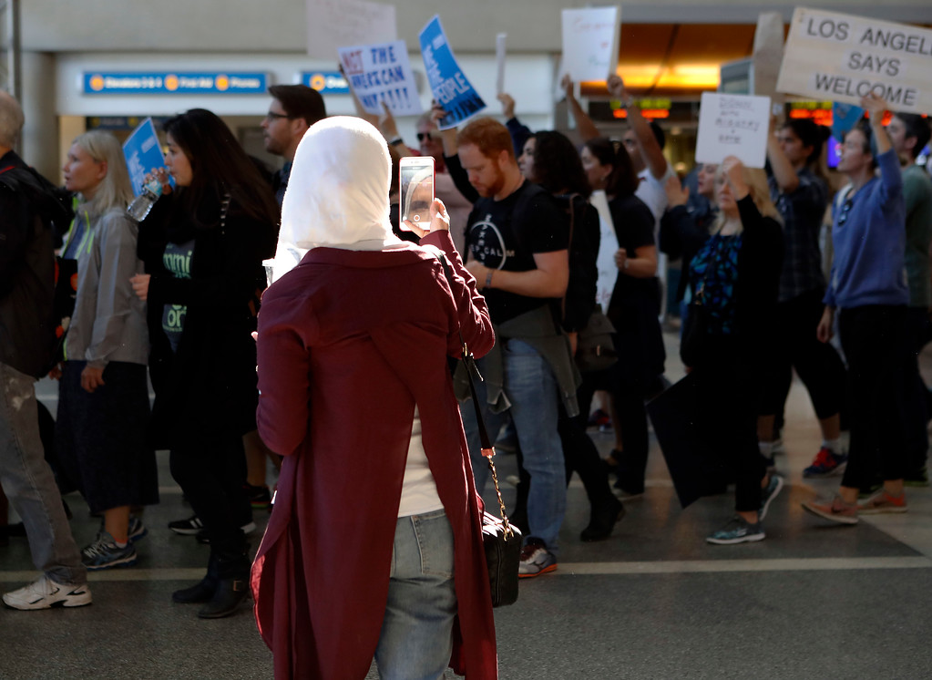 . A traveler records demonstrators as they march through Tom Bradley International Terminal as protests against President Donald Trump\'s executive order banning travel from seven Muslim-majority countries continue at Los Angeles International Airport Sunday, Jan. 29, 2017. (AP Photo/Ryan Kang)