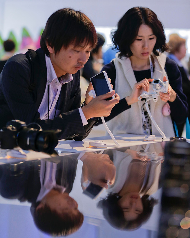 . Trade show attendees examine the Samsung Galaxy Camera 2 at the International Consumer Electronics Show, Wednesday, Jan. 8, 2014, in Las Vegas. (AP Photo/Julie Jacobson)
