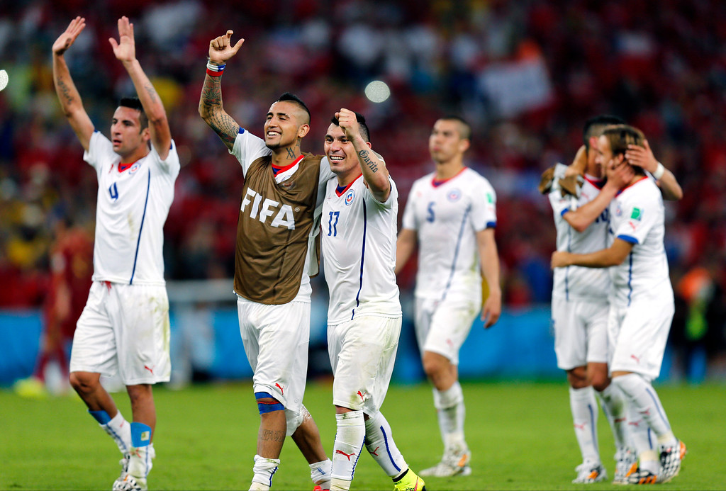 . Chile\'s national team celebrate after their victory over Spain during the group B World Cup soccer match between Spain and Chile at the Maracana Stadium in Rio de Janeiro, Brazil, Wednesday, June 18, 2014. Defending champion Spain was eliminated from the World Cup after losing to Chile 2-0. (AP Photo/Frank Augstein)