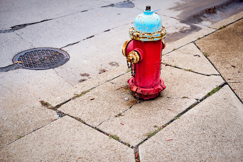 A red fire hydrant with a bluish top surrounded by cracks and concrete slab gaps in Pittsburg.