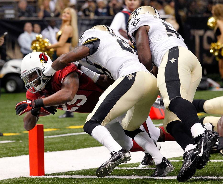 . Arizona Cardinals running back Alfonso Smith (29) dives over the goal line to score a touchdown as New Orleans Saints cornerback Keenan Lewis (28) and outside linebacker David Hawthorne (57) defend in the first half of an NFL football game in New Orleans, Sunday, Sept. 22, 2013. (AP Photo/Gerald Herbert)