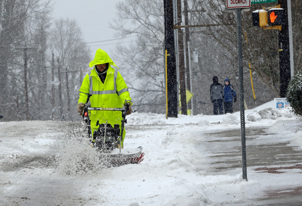 . A city worker removes snow from a crosswalk as a winter storm blankets the area in Carrboro, N.C., Saturday, Jan. 7, 2017.   Snow and sleet pounded a large swath of the East Coast on Saturday, coating roads with ice and causing hundreds of crashes  (AP Photo/Gerry Broome)