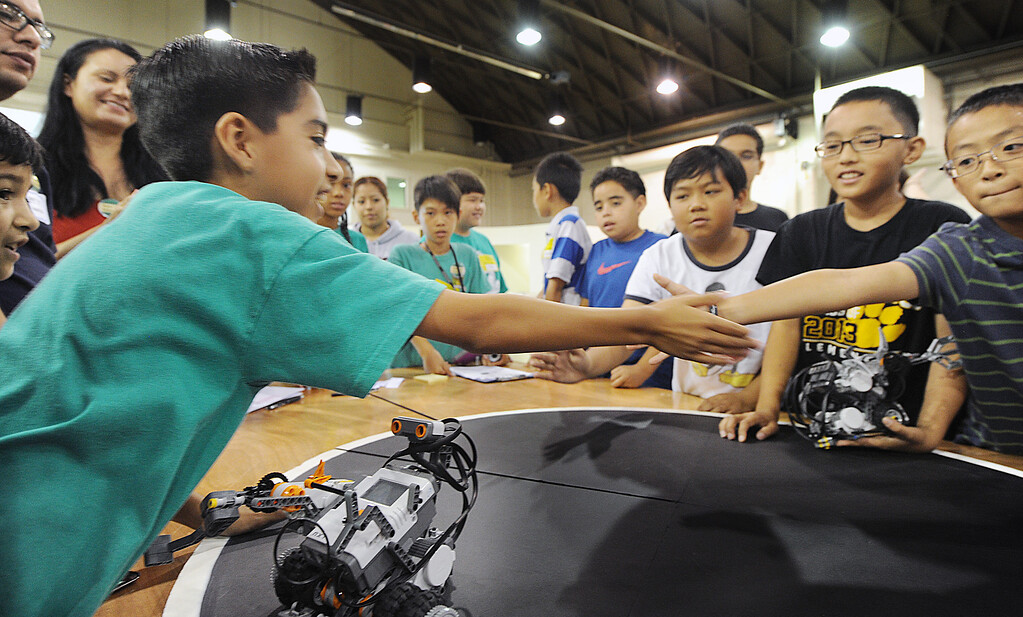 """. Daniel Baca, Kings ley Elementary School in Pomona, left, with his team robot, \""""Speedy McMean\"""", won the competition against Collegewood Elementary, and receives congratulations from Tyler Xu, whose robot, \""""Exterminators\"""" finished second. Cal Poly Pomona\'s Robotics Initiative invited 200 elementary and middle school students to a Robot Expo at LA Fairplex in Pomona Monday, May 20, 2013.(SGVN/Photo by Walt Mancini)Cal Poly Pomona\'s Robotics Initiative invited 200 elementary and middle school students to a Robot Expo at LA Fairplex in Pomona Monday, May 20, 2013. (SGVN/Photo by Walt Mancini)"""