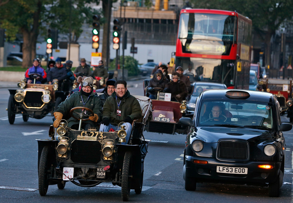 . Participants drive their cars amidst traffic in central London, during the London to Brighton Veteran Car Run, Sunday, Nov. 3, 2013. Over 400 pre-1905 vehicles made their way on the historic 60-mile run from Hyde Park in London to coastal Brighton in southern England, in the world\'s longest running motoring celebration spanning 117 years. (AP Photo/Lefteris Pitarakis)