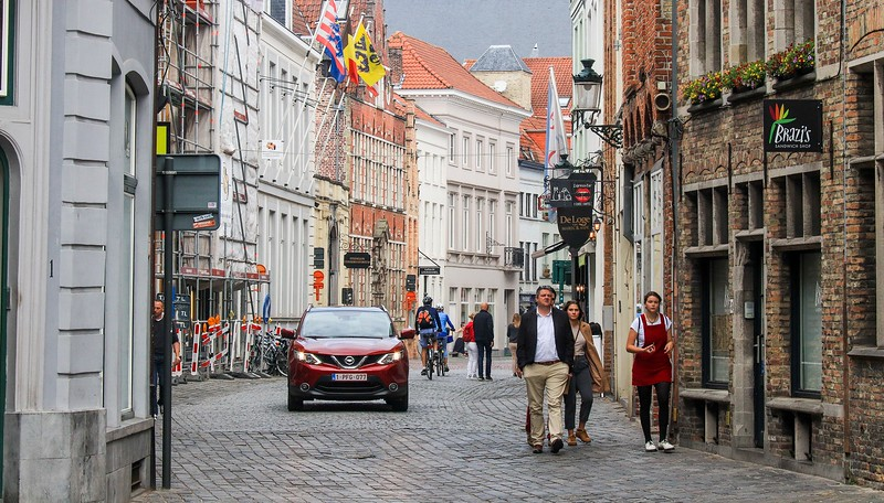 Cars, bikes, and pedestrians all run together on Bruges streets.
