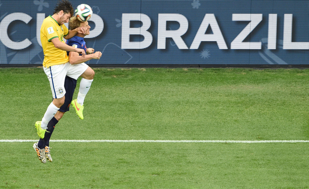. Brazil\'s defender Maxwell (L) and Netherlands\' defender Dirk Kuyt vie for the ball during the third place play-off football match between Brazil and Netherlands during the 2014 FIFA World Cup at the National Stadium in Brasilia on July 12, 2014. (EVARISTO SA/AFP/Getty Images)
