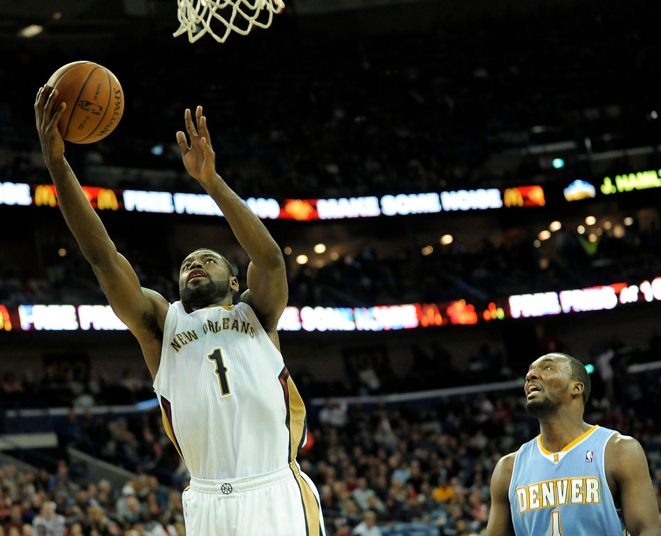 . New Orleans Pelicans guard Tyreke Evans (1) scores two of his game high 19 points in front of Denver Nuggets guard Jordan Hamilton (1) in the second half of an NBA basketball game in New Orleans, Friday, Dec. 27, 2013. New Orleans won 105-89. (AP Photo/Stacy Revere)