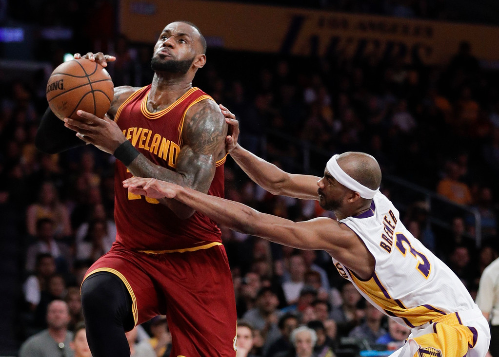 . Cleveland Cavaliers\' LeBron James, left, drives to the basket under defense by Los Angeles Lakers\' Corey Brewer during the second half of an NBA basketball game Sunday, March 19, 2017, in Los Angeles. The Cavaliers won 125-120. (AP Photo/Jae C. Hong)