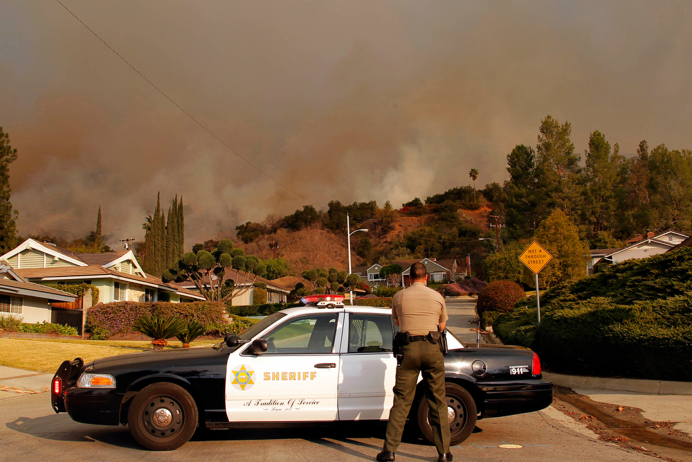 . An Los Angeles County Sheriff blocks a road in a neighborhood while a wildfire burns in the hills just north of the San Gabriel Valley community of Glendora, Calif. on Thursday, Jan 16, 2014. Southern California authorities have ordered the evacuation of homes at the edge of a fast-moving wildfire burning in the dangerously dry foothills of the San Gabriel Mountains. (AP Photo/Nick Ut)