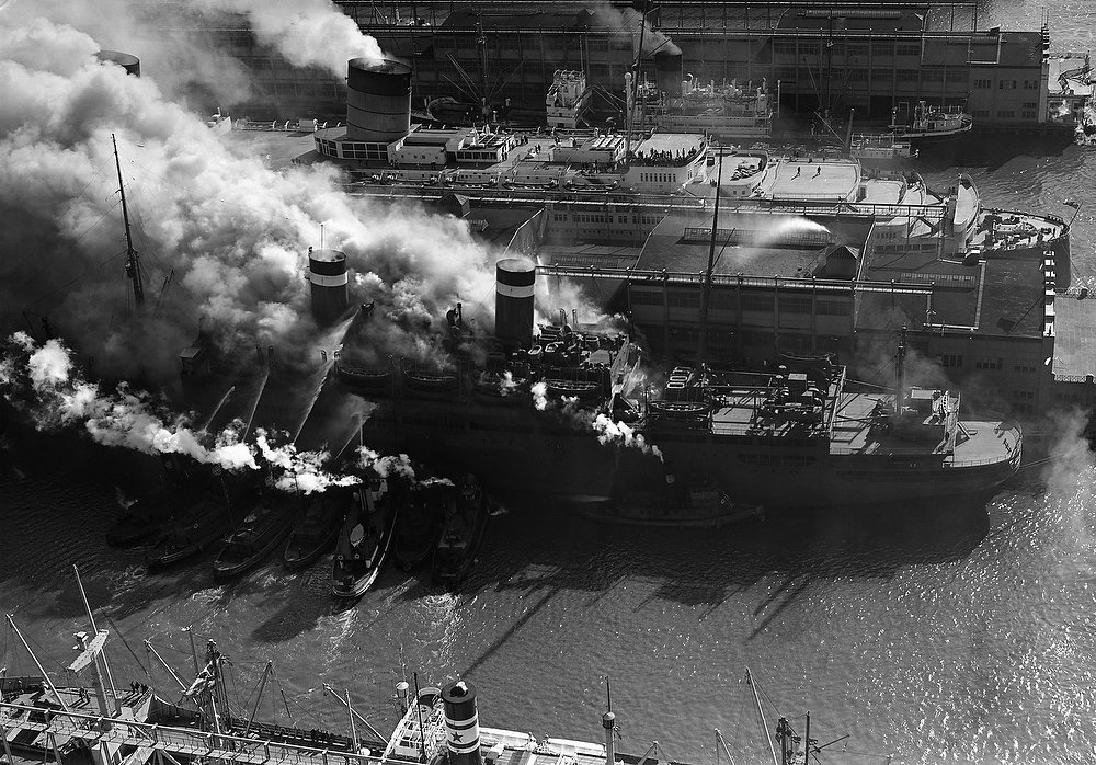 Description of . Fireboats pour water into the burning U.S. liner John Ericsson at Pier 90 in New York on March 7, 1947. The British liner Queen Elizabeth is in background. (AP Photo).
