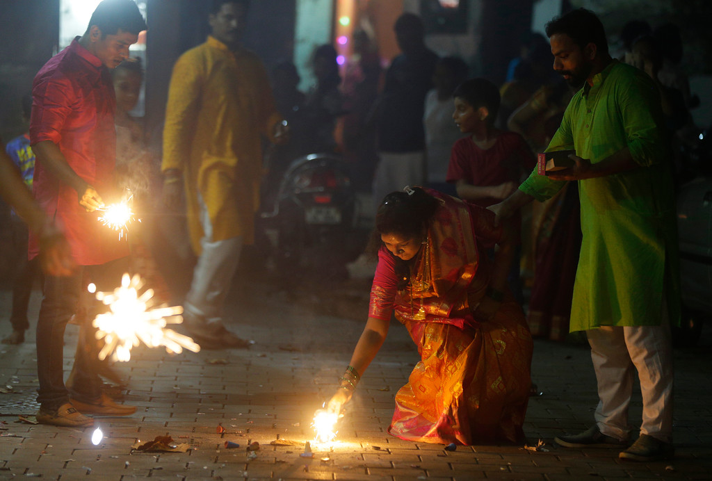 . Indians light firecrackers to celebrate Diwali, the Hindu festival of lights, in Mumbai India, Thursday, Oct. 19, 2017. (AP Photo/Rafiq Maqbool)