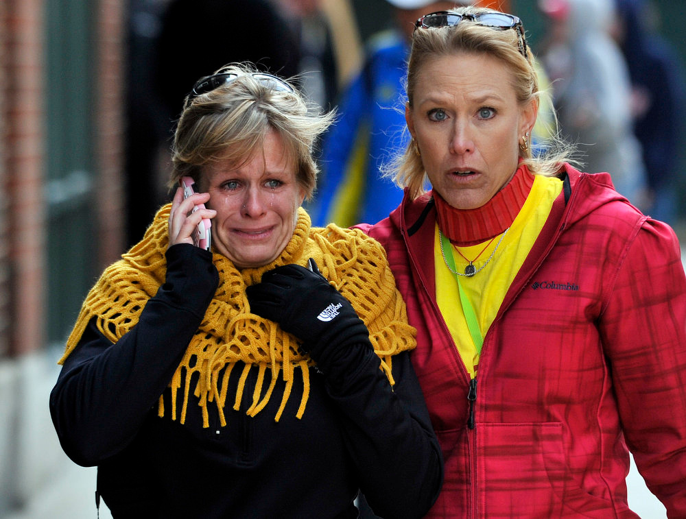 . Women react as they walk from the area where there was an explosion after the Boston Marathon in Boston, Monday, April 15, 2013. (AP Photo/Josh Reynolds)