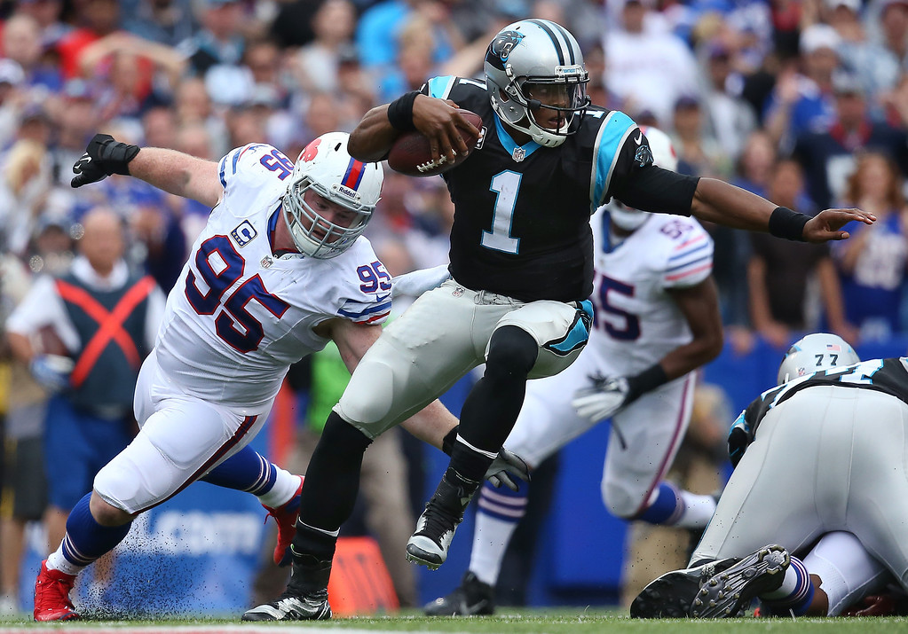 . Cam Newton #1 of the Carolina Panthers escapes pressure during NFL game action from Kyle Williams #95 of the Buffalo Bills at Ralph Wilson Stadium on September 15, 2013 in Orchard Park, New York. (Photo by Tom Szczerbowski/Getty Images)