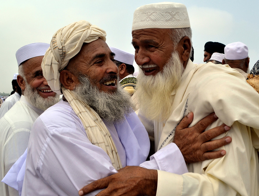 . Afghan refugees living in Peshawar, Pakistan, greet each other during the Eid al-Fitr holiday that marks the end of the holy fasting month of Ramadan, Thursday, Aug. 8, 2013. Millions of Muslims began celebrating the end of Ramadan on Thursday with morning prayers. (AP Photo/Mohammad Sajjad)