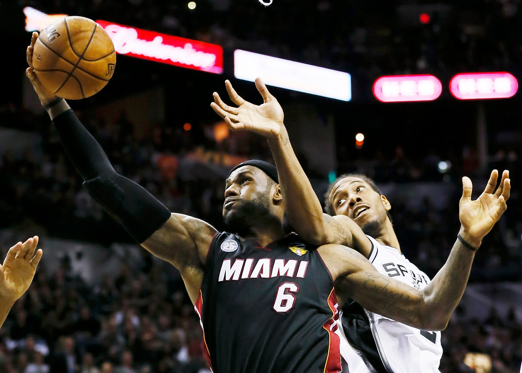 . Miami Heat\'s LeBron James (L) rebounds against San Antonio Spurs\' Kawhi Leonard during the third quarter in Game 4 of their NBA Finals basketball series in San Antonio, Texas June 13, 2013. REUTERS/Lucy Nicholson