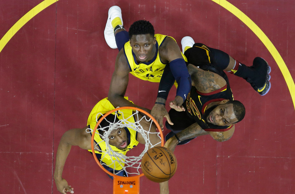 . Cleveland Cavaliers\' LeBron James, right, and Indiana Pacers\' Thaddeus Young, left, and Victor Oladipo watch the ball enter the basket in the first half of Game 5 of an NBA basketball first-round playoff series, Wednesday, April 25, 2018, in Cleveland. The Cavaliers won 98-95. (AP Photo/Tony Dejak)