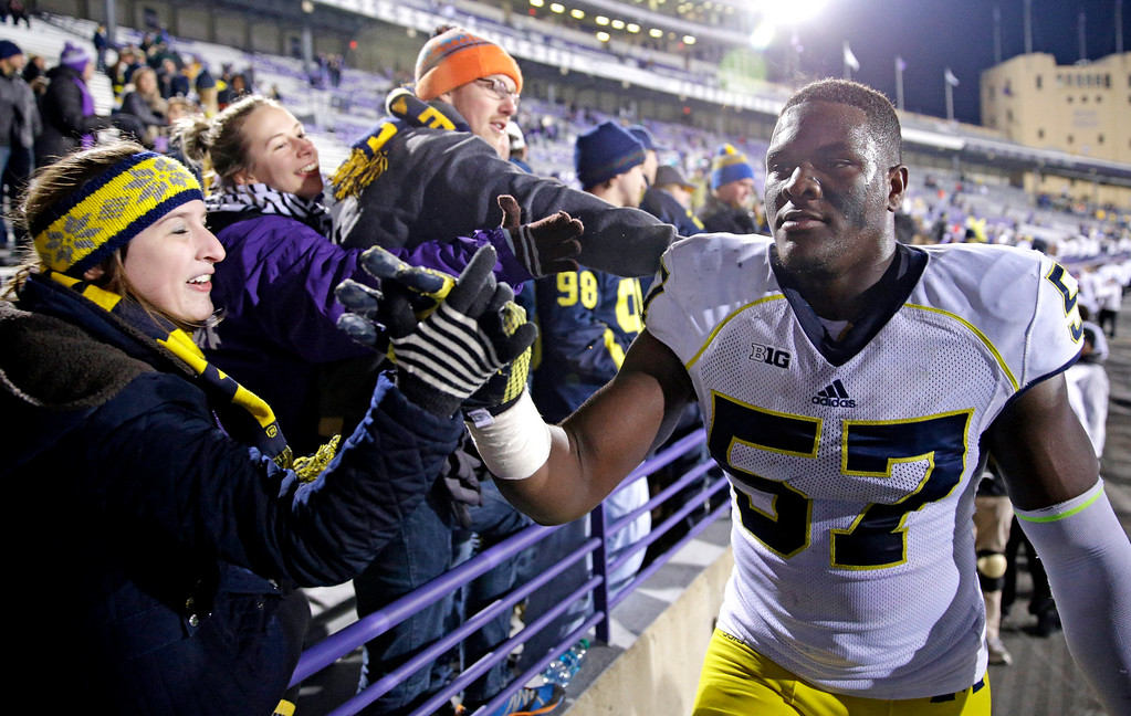 . Michigan defensive end Frank Clark (57) celebrates with fans  after Michigan defeated Northwestern 10-9 in an NCAA college football game in Evanston, Ill., Saturday, Nov. 8, 2014. (AP Photo/Nam Y. Huh)