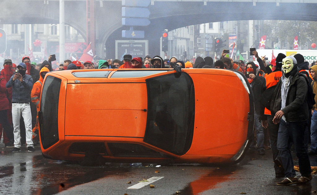 . Protestors overturn a car on November 6, 2014 in Brussels, during a huge march, the first mass protest against the new centre-right government\'s austerity policies.    AFP PHOTO / JOHN THYS/AFP/Getty Images