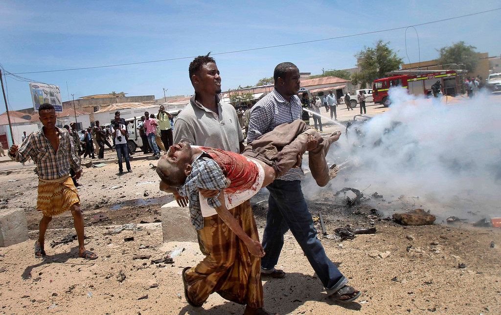 . Somali men carry a seriously wounded man after a car bomb blast close to the Somali government\'s headquarters in the capital Mogadishu, Somalia Monday, March 18, 2013. An explosives-laden car that apparently was targeting a truck full of Somali government officials instead hit a civilian car and exploded, setting a nearby mini-bus on fire and killing at least seven people.  (AP Photo/Farah Abdi Warsameh)