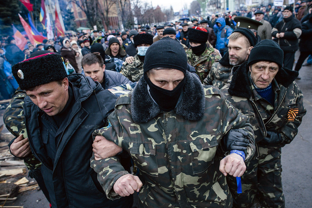 . Pro-Russian activists escort a man (unseen) who they say is a provocateur outside the secret service building in the eastern Ukrainian city of Lugansk on April 13, 2014. Ukraine\'s interior minister said on April 13 that both sides had suffered casualties during a raid launched by Ukrainian special forces on a police station in the eastern city of Slavyansk that was seized by pro-Russian gunmen. AFP PHOTO / DIMITAR DILKOFF