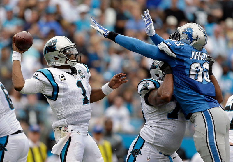 . Carolina Panthers\' Cam Newton (1) throws a pass under pressure from Detroit Lions\' George Johnson (93) during the second half of an NFL football game in Charlotte, N.C., Sunday, Sept. 14, 2014. (AP Photo/Bob Leverone)