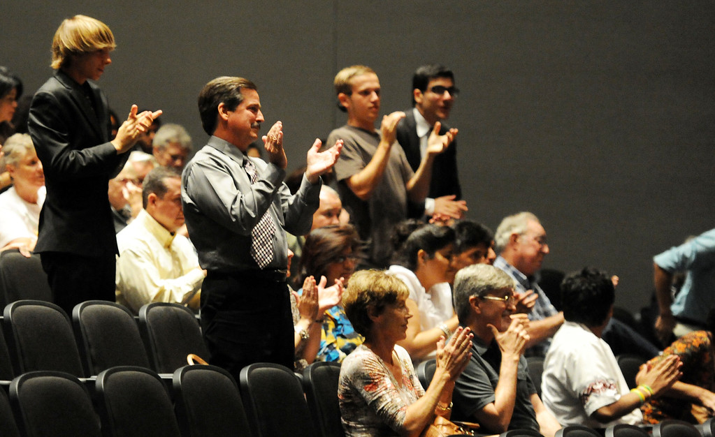 . Former cross-country coach James O\'Brien claps along with others after girls cross-country coach Michael Feraco-Eberle (not pictured) spoke as over 200 people crowded the Arcadia Unified School District Performing Arts Center as a show of support for fired Arcadia High School cross-country coach James O\'Brien during a Arcadia Unified School District Board of Education meeting on Tuesday, July 23, 2013 in Arcadia, Calif. O\'Brien, led the team to two time state and national championships.  (Keith Birmingham/Pasadena Star-News)