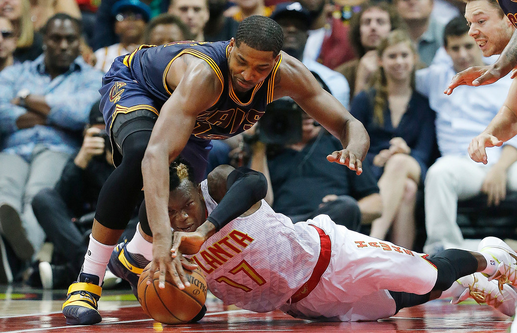 . Cleveland Cavaliers center Tristan Thompson (13) and Atlanta Hawks guard Dennis Schroder (17) vie for a loose ball in the second half of Game 4 of the second-round NBA basketball playoff series, Sunday, May 8, 2016, in Atlanta. The Cleveland Cavaliers won 100-99. (AP Photo/John Bazemore)