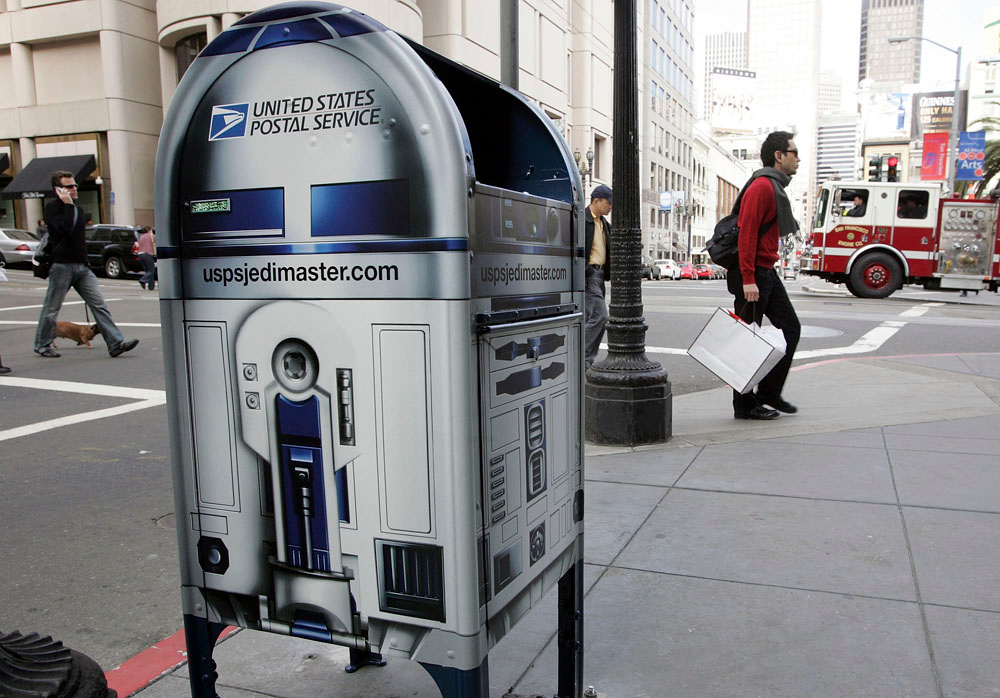 Description of . People walk by a US Postal Service mailbox designed to look like Star Wars character R2-D2 March 18, 2007 in San Francisco, California. The U.S. Postal Service has wrapped select mailboxes in 200 US cities as part of an ad campaign to promote a new Star Wars stamp set that is to be unveiled on March 28.  (Photo by Justin Sullivan/Getty Images)
