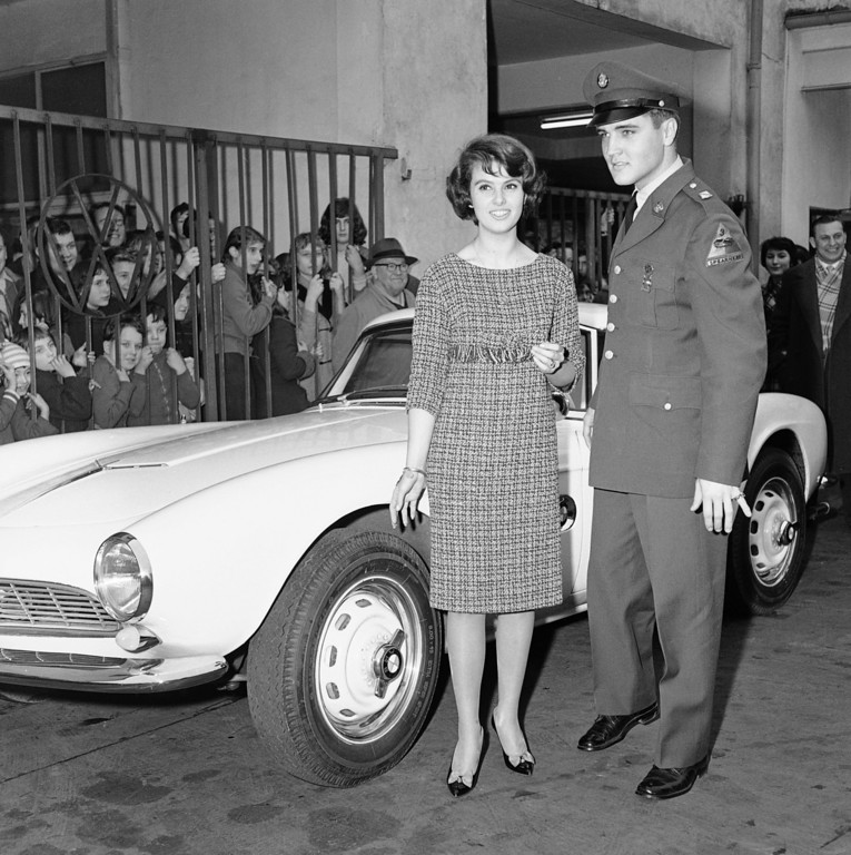 . Pfc. Elvis Presley shown with Ursula Siebert in front of German sports car at Frankfurt, West Germany, auto agency on Dec. 20, 1958. Curious youngsters crowd railing at left for a look at Elvis who is stationed on base at nearby Friedberg. The car, a BMW 507, made by the Bavarian Motor Co., is a sleek two-seater, painted white on the outside and upholstered with white and black leather inside. Dealer said he had sold the car, a used demonstration model, to Elvis for $3,750. When new, it could cost about $7,500. (AP Photo/Kurt Strumpf)