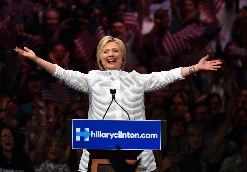 """. Democratic presidential candidate Hillary Clinton acknowledges celebratory cheers from the crowd during her primary night event at the Duggal Greenhouse, Brooklyn Navy Yard, June 7, 2016 in New York.  Hillary Clinton hailed a historical \""""milestone\"""" for women as she claimed victory over rival Bernie Sanders in the Democratic White House nomination race. \""""Thanks to you, we\'ve reached a milestone,\"""" she told cheering supporters at a rally in New York. \""""The first time in our nation\'s history that a woman will be a major party\'s nominee.\"""" (TIMOTHY A. CLARY/AFP/Getty Images)"""