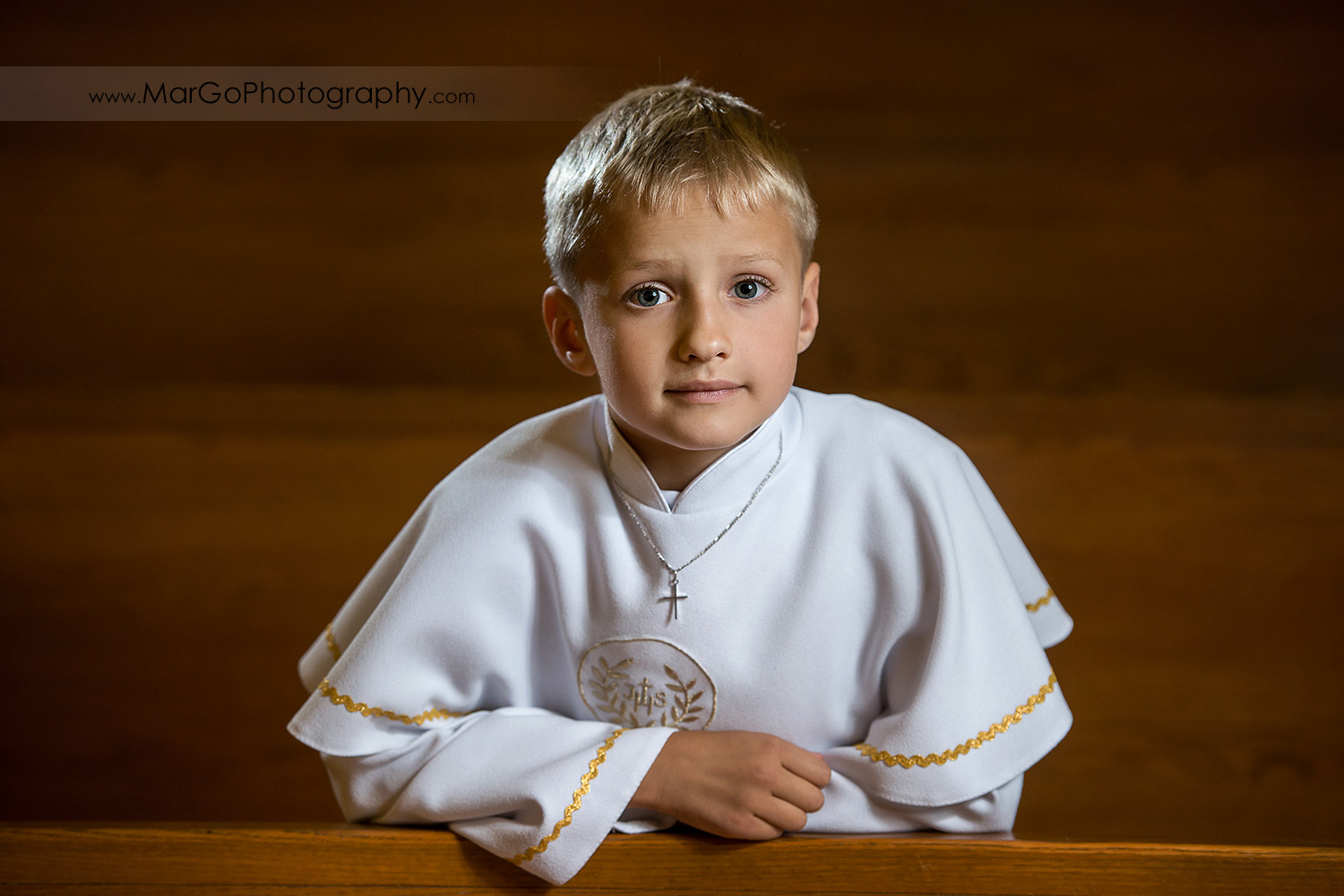 first communion boy in white alb in wooden San Jose church pews