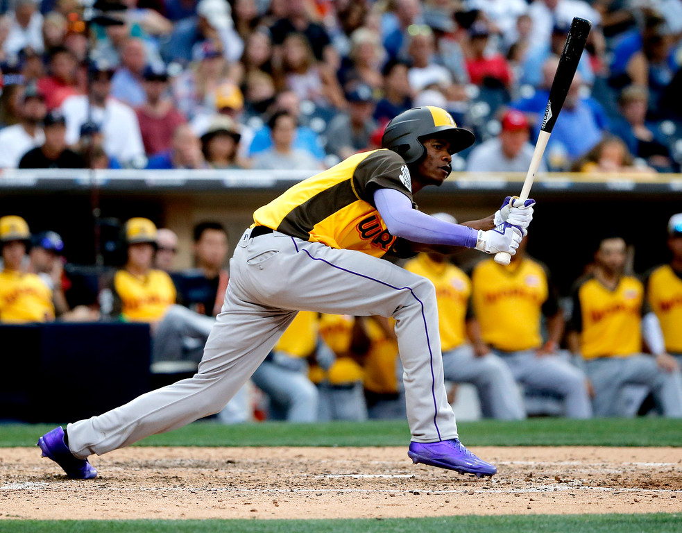 . World Team\'s Raimel Tapia, of the Colorado Rockies, follows through on an RBI base hit during the ninth inning of the All-Star Futures baseball game, Sunday, July 10, 2016, in San Diego. (AP Photo/Lenny Ignelzi)