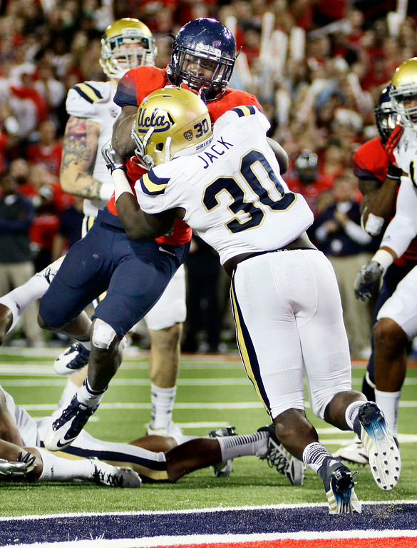 . Arizona\'s Ka\'Deem Carey, behind, drives to the endzone for a touchdown while UCLA\'s Myles Jack (30) holds on in the first half of an NCAA college football game, Saturday, Nov. 9, 2013 in Tucson, Ariz.  (AP Photo/Wily Low)