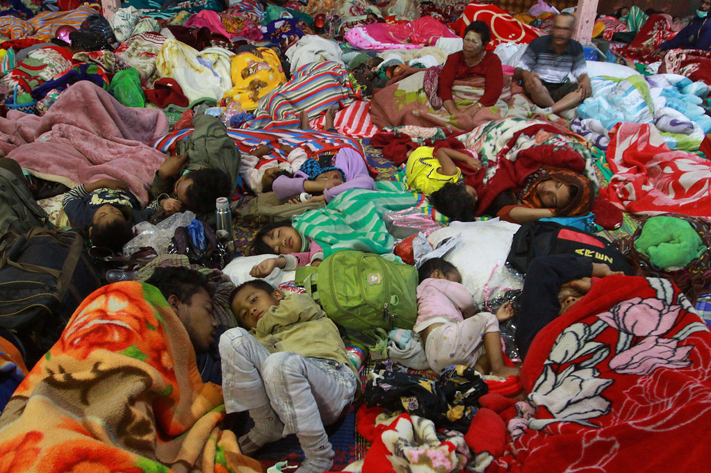 . Indonesian evacuees displaced by Mount Sinabung volcano eruption sleeps in cramped condition in an evacuation center in Karo district on September 16, 2013.  Thousands of villagers fled on September 15, 2013 after Sinabung volcano erupted on Indonesia\'s Sumatra island spewing rocks and red-hot ash onto surrounding villages, officials said.  The volcano was dormant for nearly 100 years before erupting in August and September 2010, forcing about 12,000 people to flee.   KHARISMA TARIGAN/AFP/Getty Images
