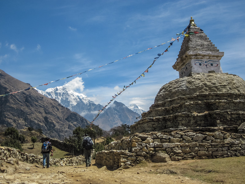 Two Nepalis walk past a stupa on a pass between Khumjung and Namche Bazaar in the Himalayas of Nepal