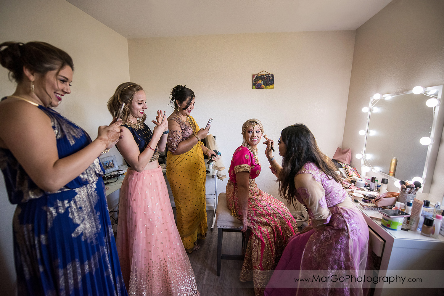 bridesmaids photographing Indian bride during makeup
