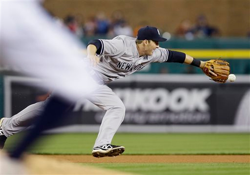 . New York Yankees shortstop Stephen Drew tosses the ball to second baseman Gregorio Petit for the out on Detroit Tigers\' Ian Kinsler during the sixth inning of a baseball game, Tuesday, April 21, 2015, in Detroit. (AP Photo/Carlos Osorio)