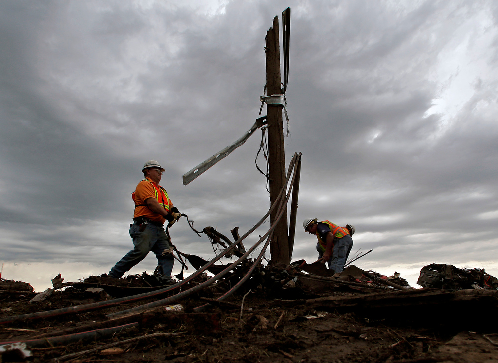 . AT&T employees sort through tangled phone lines as they clean up in a tornado-ravaged neighborhood Tuesday, May 21, 2013, in Moore, Okla. A huge tornado roared through the Oklahoma City suburb Monday, flattening entire neighborhoods and destroying an elementary school with a direct blow as children and teachers huddled against winds. (AP Photo/Charlie Riedel)