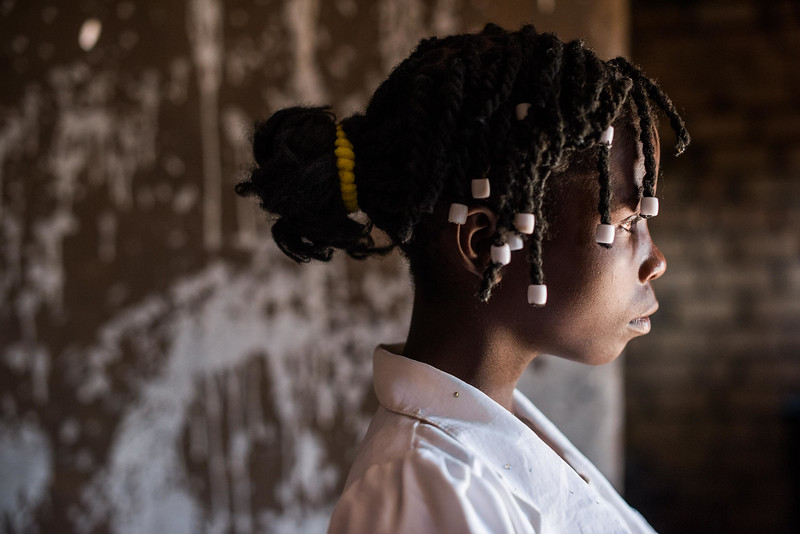 """Portrait of Kapinga Alphoncine, 13 yr-old girl.  She lives with her grandmother, Kapinga Godelive, 66 and her 3 brothers: 1-Francois Ngondo, 14 2-Mbuyamba Phillip, 9 3-Beya Honore, 6 Kananga, DRC Democratic Republic of Congo.  Inside Kapinga's four-room house the walls are paint splattered. There is little furniture except for two small tables and an old cabinet. On top sits a dusty old television. A peek behind reveals that it has no cord. Kapinga sits on a low, wooden bench against one wall reading an old school exercise book of English lessons. """"Good morning my friends, good morning.""""  Her English is good in spite of a mispronunciation here and there. High up on the wall to the right is a crucifix. It's as battle worn as the rest of the house. Light streams in through the numerous holes in the tin-sheeted roof. In the yard outside, the house is ringed on all sides with gardens of potato and cassava leaves, sorrel and sugarcane among other things.  In one corner of the yard a few visitors gather on homemade chairs under a thatched-roof patio. Across the compound the afternoon sun throws light on the smaller of the two buildings there. In chalk, just below the roof line are the words, """"Il n'ya pas de rose sans epines."""" There is no rose without thorns.  Home Life Her family is living with her grandmother since her dad died. Her mom went off to look for work. She has 3 brothers,1 older and 2 younger. 1-Francois Ngondo, 14 2-Mbuyamba Phillip, 9 3-Beya Honore, 6  She helps her grandmother by sweeping the compound, washing dishes, working in the garden and doing a little cooking. Kapinga sleeps on tattered sheets of plastic. She also puts down a mosquito net but sleeps on top of it.  School Kapinga doesn't attend school right now. She used to but had to stop when her father died because they don't have the money for school fees. She was in grade 7 which is the first grade of high school in the DRC.  She liked school and especially learning English and French.  She still"""