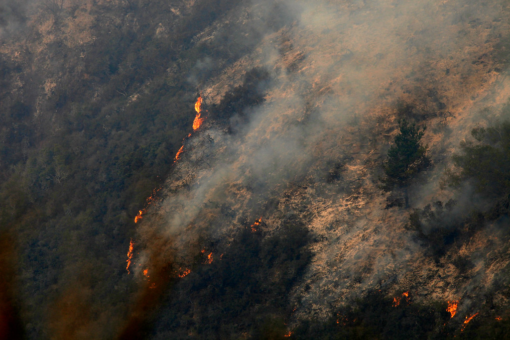 . Flames creep down a hillside as firefighters battle a fire in the Pfeiffer Ridge area in Big Sur, Calif. on Tuesday December 17, 2013. (Photo David Royal/ Monterey County Herald)