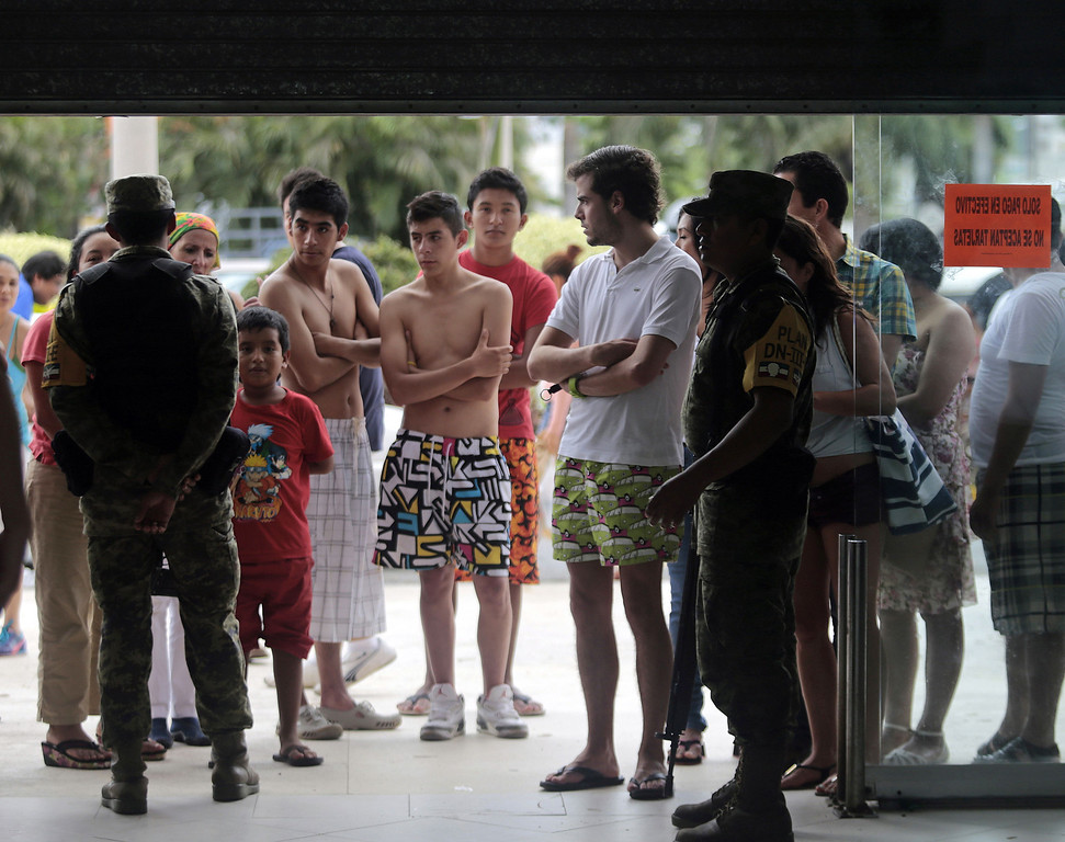 . Residents and tourists queue to buy supplies outside a supermarket guarded by soldiers in Acapulco, state of Guerrero, Mexico, after heavy rains hit the area on September 17, 2013. Mexican officials launched an airlift to evacuate tens of thousands of tourists stranded in the flooded resort of Acapulco on Tuesday following a pair of deadly major storms. The official death toll rose to 47 after the tropical storms, Ingrid and Manuel, swarmed large swaths of the country during a three-day holiday weekend, sparking landslides and causing rivers to overflow in several states.  Pedro PARDO/AFP/Getty Images
