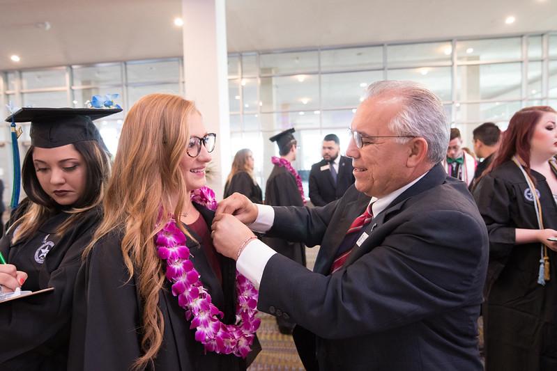 Sarah Wright recieves her Islander Alumni pin from Haysam Dawood.