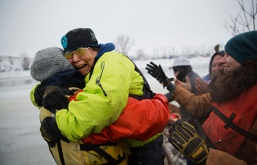 . In this Thursday, Dec. 1, 2016 photo, Patty Sam Porter of Colville, Wash., and a member of the Colville Native American tribe, is embraced upon reaching shore by canoe at the Oceti Sakowin camp where people have gathered to protest the Dakota Access oil pipeline in Cannon Ball, N.D. Porter traveled from Montana with fellow tribal members on canoe for 10 days down the Missouri river to reach the camp. (AP Photo/David Goldman)