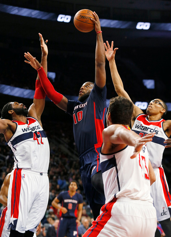 . Detroit Pistons forward Greg Monroe (10) shoots between Washington Wizards forward Nene Hilario (42), Kris Humphries (43) and Otto Porter Jr. in the first half of an NBA basketball game in Auburn Hills, Mich., Sunday, Feb. 22, 2015. (AP Photo/Paul Sancya)