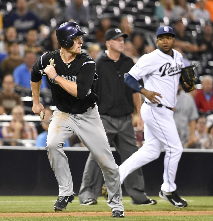. SAN DIEGO, CA - AUGUST 12:  Justin Morneau #33 of the Colorado Rockies gets caught in a run down as Odrisamer Despaigne #40 of the San Diego Padres covers third base during the fourth inning of a baseball game at Petco Park August, 12, 2014 in San Diego, California. Morneau was tagged out on the play.   (Photo by Denis Poroy/Getty Images)