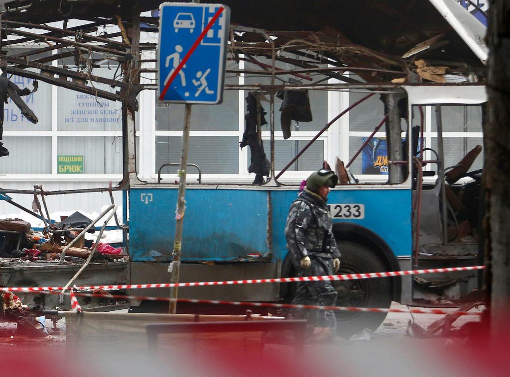 . A police officer walks along a wreckage of a trolleybus in Volgograd, Russia, Monday, Dec. 30, 2013.  A bomb blast tore through the trolleybus in the city of Volgograd on Monday morning, killing at least 14 people a day after a suicide bombing that killed at least 17 at the city\'s main railway station.  (AP Photo/Denis Tyrin)