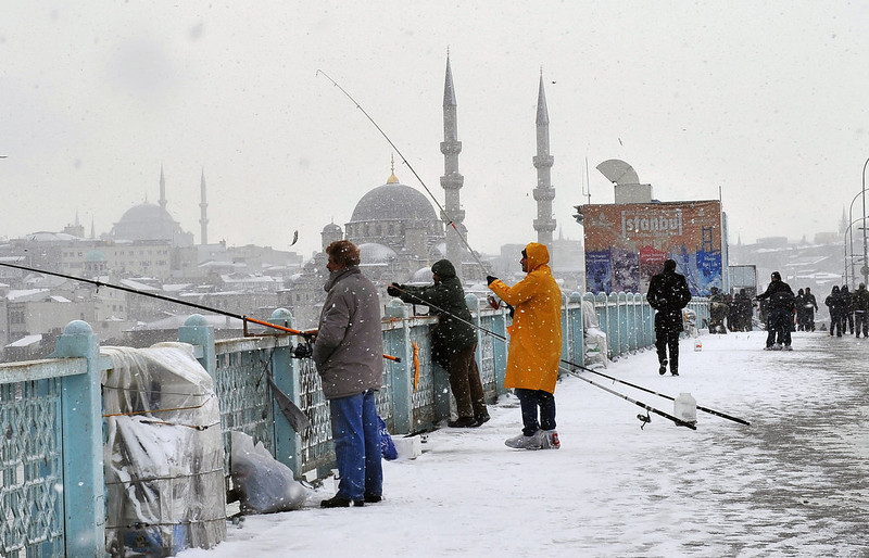 . Snow falls as people walk and anglers fish on Galata Bridge in Istanbul, on January 8, 2013. Heavy snowfall blanketed Turkey\'s commercial hub Istanbul, a city of 15 million, paralysing daily life, disrupting air traffic and land transport. Officials said the snow is expected to continue until late tomorrow, according to the weather forecast. BULENT KILIC/AFP/Getty Images