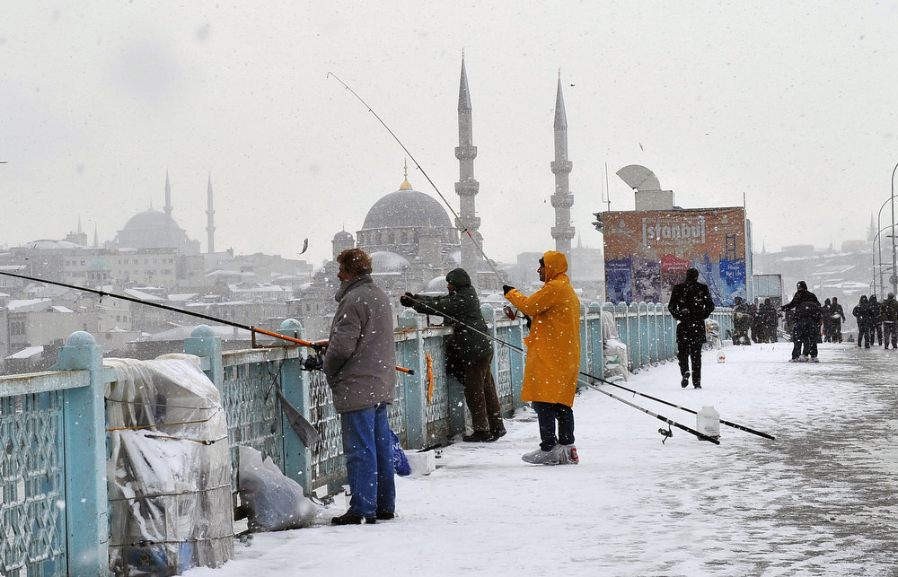 Description of . Snow falls as people walk and anglers fish on Galata Bridge in Istanbul, on January 8, 2013. Heavy snowfall blanketed Turkey's commercial hub Istanbul, a city of 15 million, paralysing daily life, disrupting air traffic and land transport. Officials said the snow is expected to continue until late tomorrow, according to the weather forecast. BULENT KILIC/AFP/Getty Images