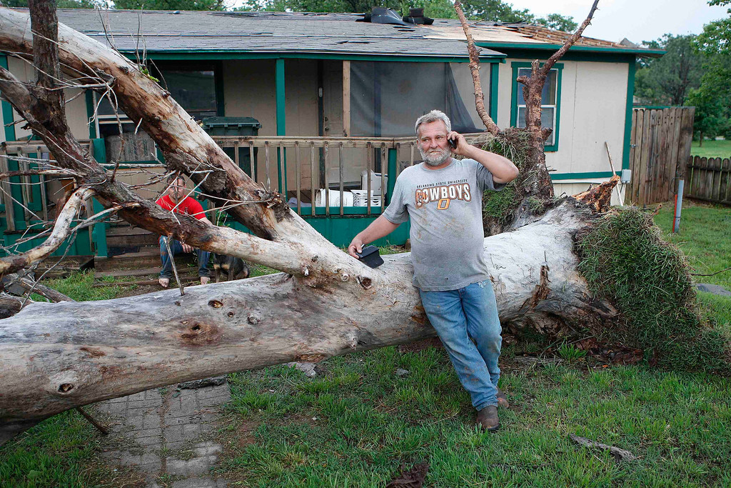 . Allen Cook talks on his cell phone as he stands next to a downed tree which missed falling on a home in a mobile home park, where several other homes were destroyed by a tornado on Sunday, west of Shawnee, Oklahoma May 19, 2013. A tornado half a mile wide struck near Oklahoma City on Sunday, part of a massive storm front that hammered the central United States. News reports said at least one person had died. REUTERS/Bill Waugh